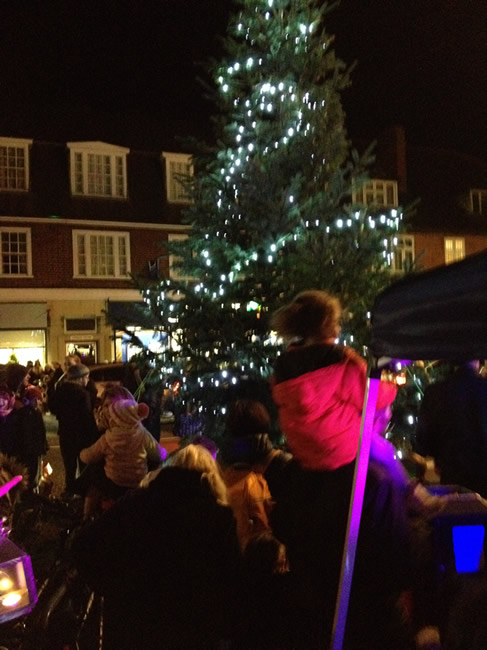 Families watch Christmas Tree Lights Switch on in Weybridge while singing carols