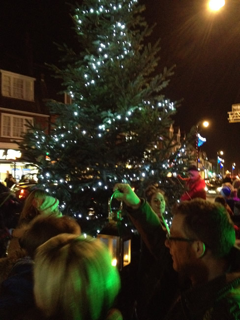 Family With Lantern at Weybridge Town Christmas Tree Lights Switch on