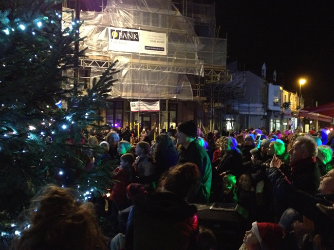 Families gather around tree for Christmas Lights Switch on with Carols in Weybridge Town Centre