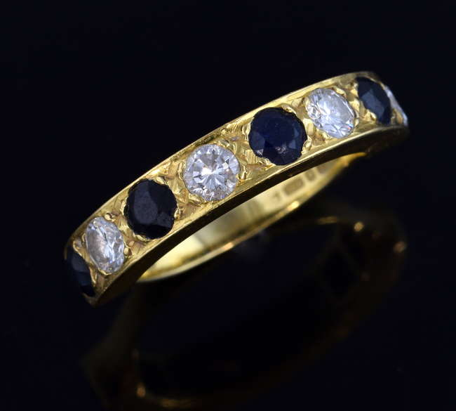 Woking Surrey Antique Jewellery Auction - Sapphire and diamond half eternity ring, the gems set in a broad band with reduced width at back, four sapphires and four diamonds total diamond weight estimated at 1.00 carat, hallmarked 18 ct