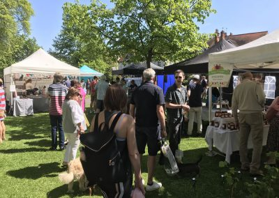 Public enjoy browsing and shopping in the sun at the stalls at the Artisan Market on Monument Green Weybridge Surrey