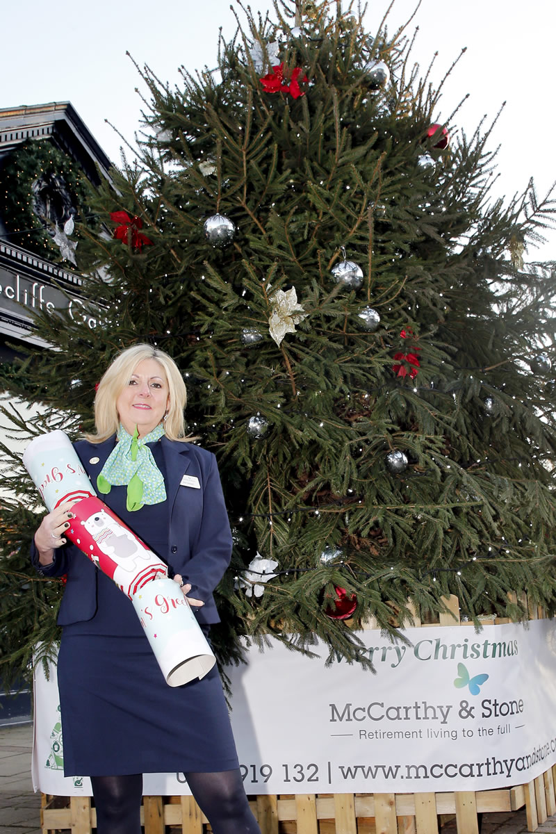 Sales Consultant Ann Stewart, next to the Christmas Tree donated to Weybridge by McCarthy and Stone