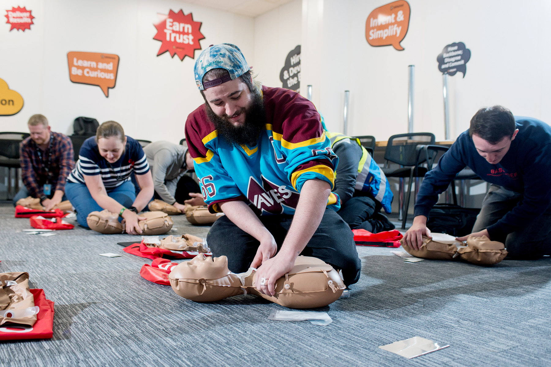 Amazon Weybridge staff practicing CPR on a dummy