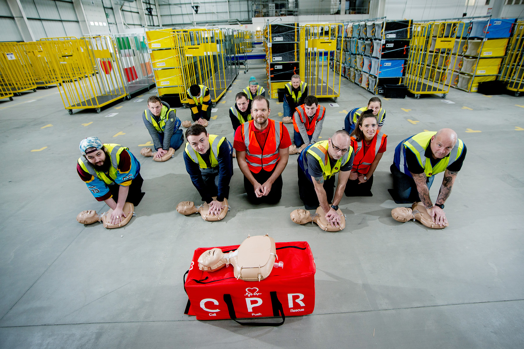 British Heart Foundation trainers teaching Weybridge Amazon workers how to become CPR trainers
