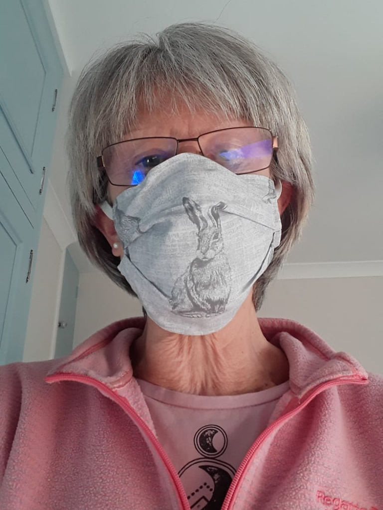 Member of Sew Weybridge  wearing a mask made by the team
