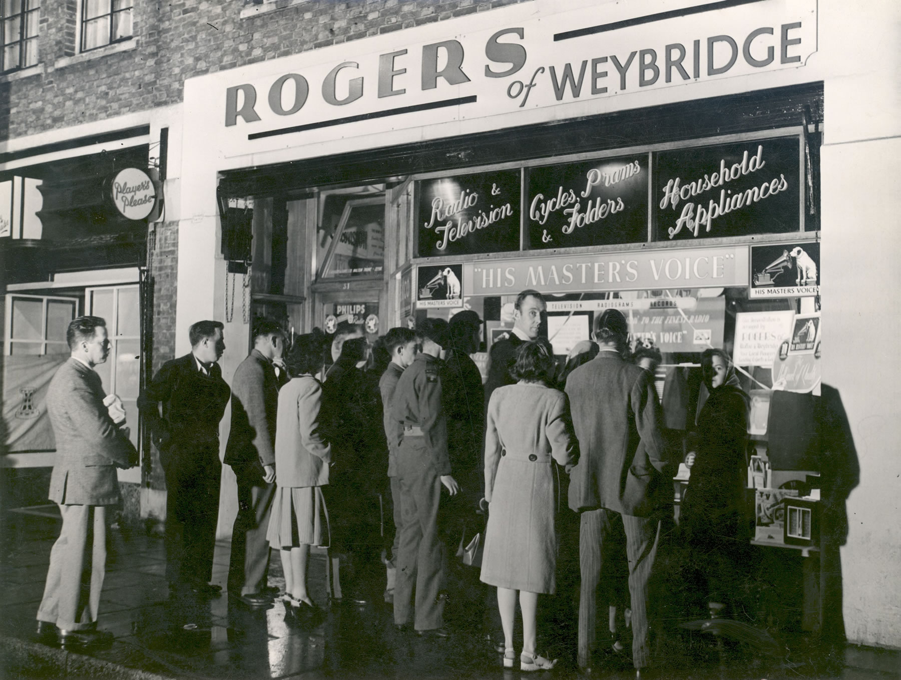Rogers of Weybridge Radio TV and Household appliances - Crowd looking at televisions in shop window Walton High Street